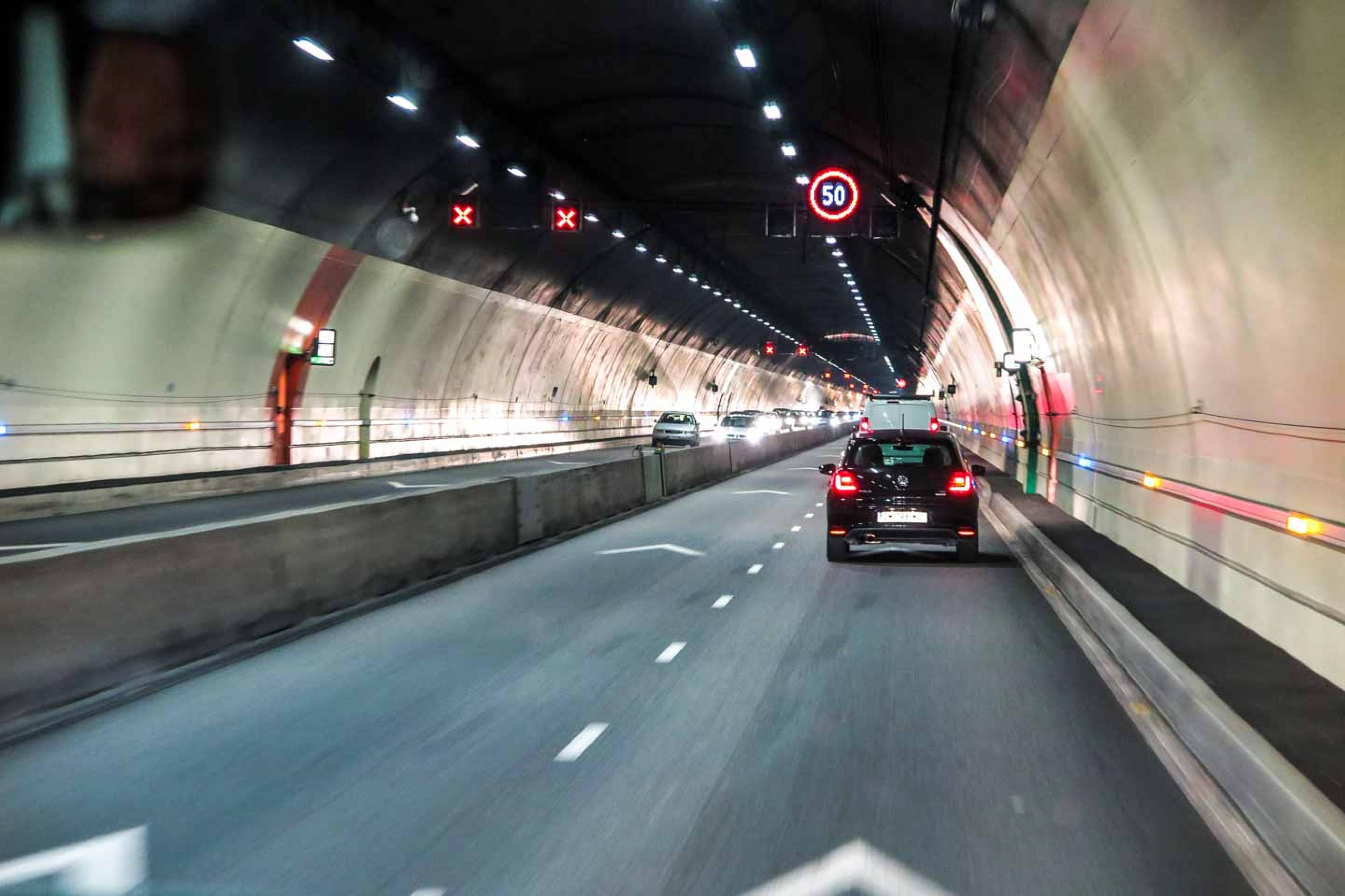 Cars drive through city road tunnel
