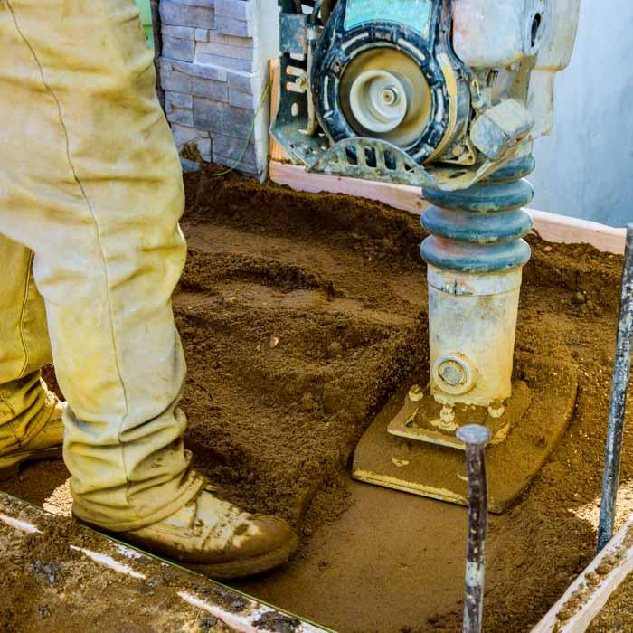 Construction worker uses vibratory hammer in dirt